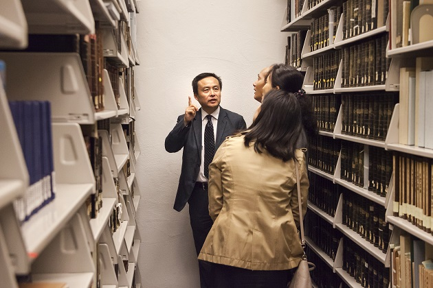 Peter X. Zhou, left, presents the library's rare book room.