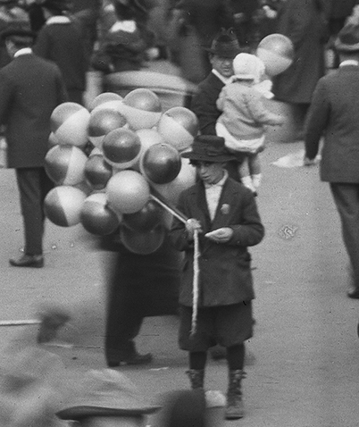 Young boy in crowd selling balloons.