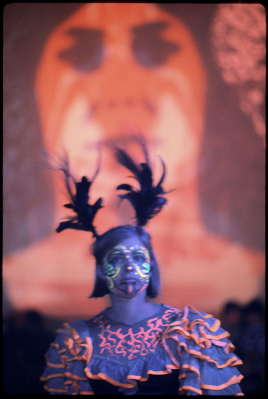 A young hippie woman with feathers that look like antlers, in day glow face paint, Avalon Ballroom, 1967] Ted Streshinsky, photographer.