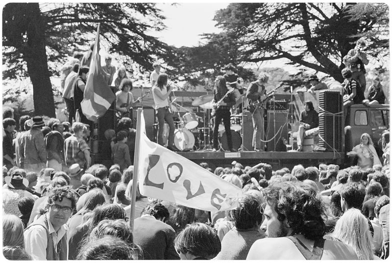 "Black and white photo of a crowd in Golden Gate Park watching a rock band on stage, with a ""Love"" banner among crowd."