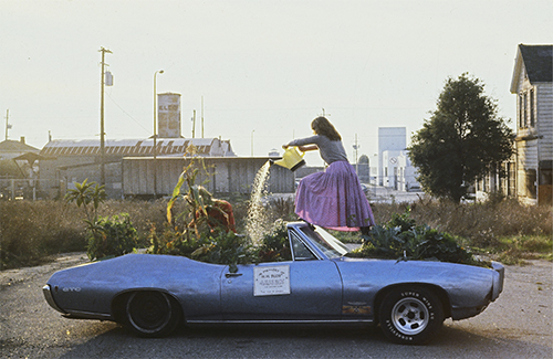 Woman watering a garden planted inside a car