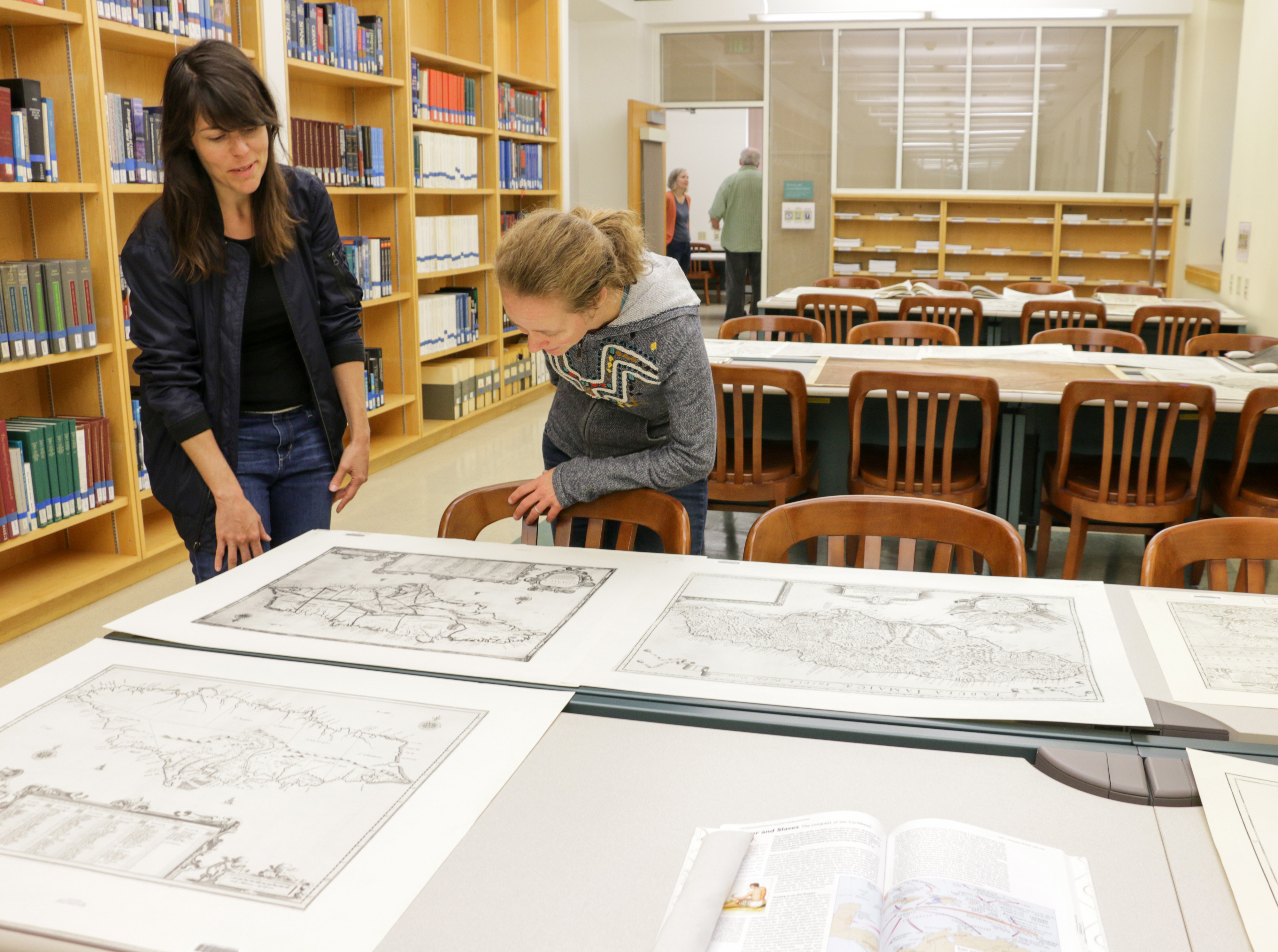 """History graduate students Nicole Viglini, left, and Amy O'Hearn discuss """"Hamilton, in Maps,"""" a pop-up exhibit Viglini helped to curate in the Earth Sciences & Map Library in McCone Hall on Sept. 22, 2017. (Photo by Jami Smith for the University Library)"""