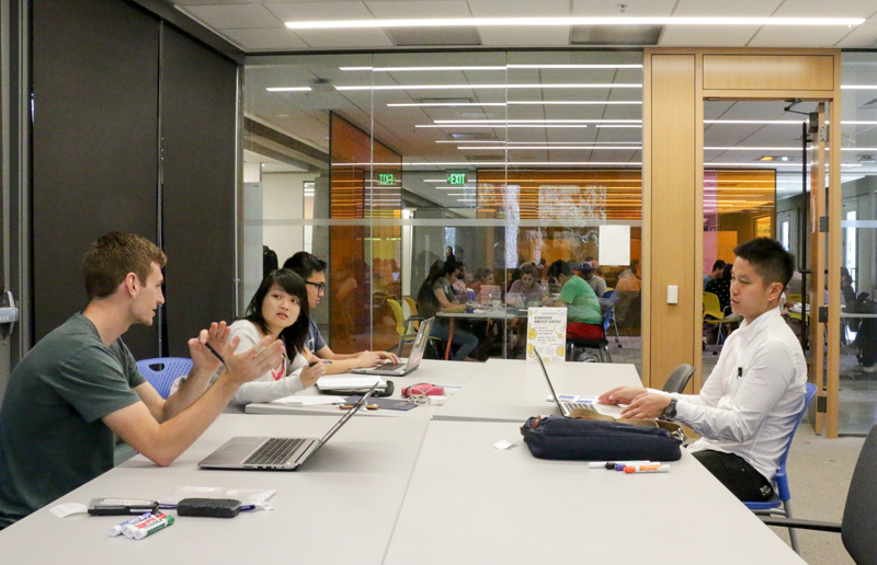 Peer adviser Ross Matthies, left, talks with data services librarian Josh Quan, right, and students Diana Ly, second from left, and Christopher Nghiem at Moffitt Library during the Data Dialogue peer advisory hours on Sept. 27, 2017. (Photo by Jami Smith for the University Library)