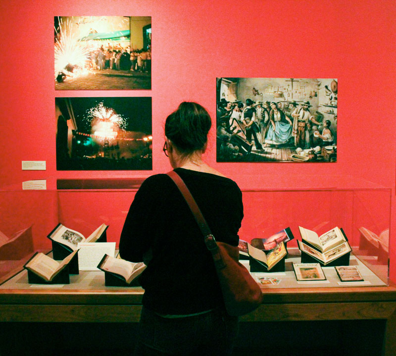 "A visitor looks at the collection during the Bancroft Library opening of the ""Viva La Fiesta"" exhibit on Oct. 12, 2017. (Photo by Jami Smith for the University Library)"