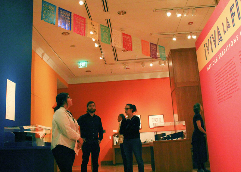 "Student Marina Henriquez, left, looks over the opening of the ""Viva La Fiesta"" exhibit, along with other visitors, in Bancroft Library on Oct. 12, 2017. (Photo by Jami Smith for the University Library)"