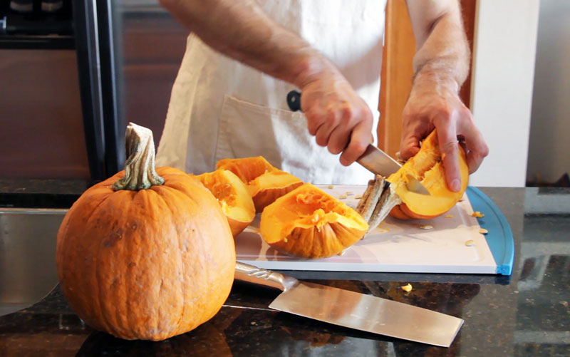 Pumpkin is cut for a pie recipe from a book held by the University Library. (Photo by Jami Smith for the University Library)