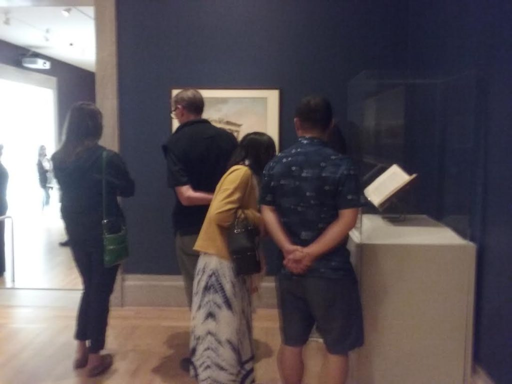 Museumgoers observe display.