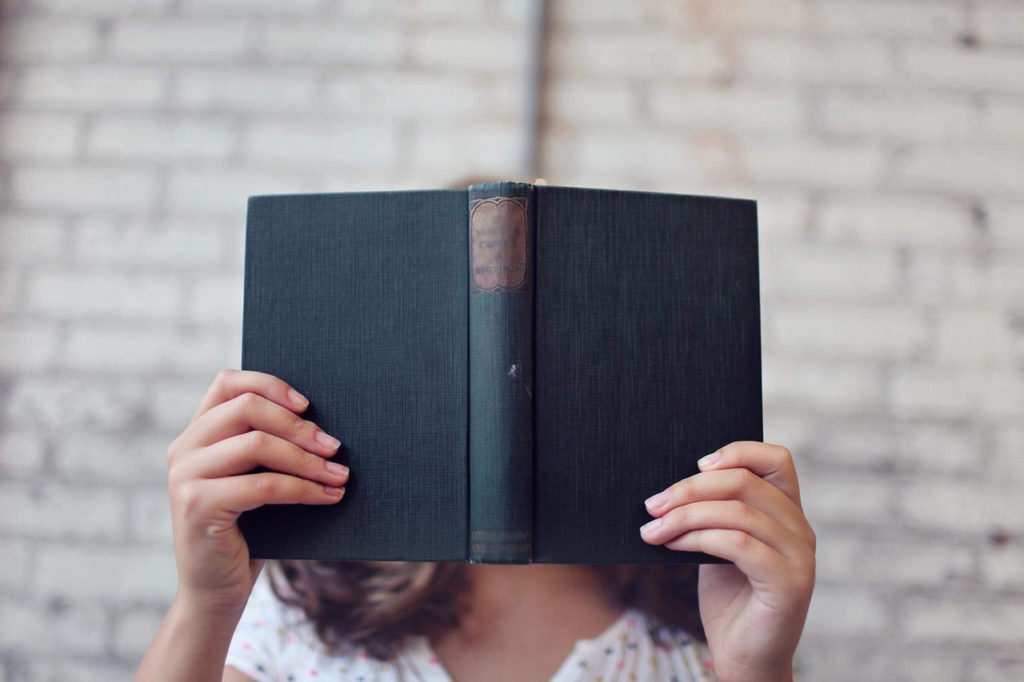 Person holding an open hardcover book in front of face
