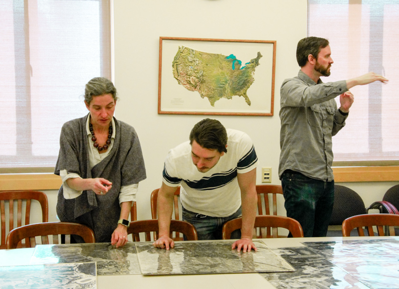 """Sam Teplitzky, left, Fernando Navarro, center, and Brian Quigley chat during the """"Mapping the University"""" event at the Earth Sciences and Map Library on Friday, Feb. 2, 2018. The event is part of the library's Maps and More series. (Photo by Jami Smith for the University Library)"""