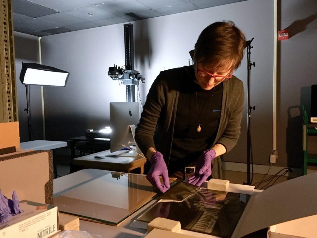Staff re-assembling broken glass negatives in the digital imaging lab