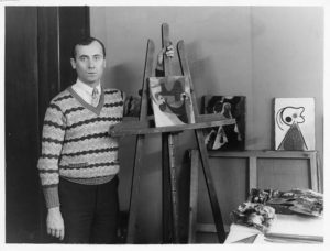 Portrait of Joan Miro with three paintings in his Paris studio. Circa 1930.