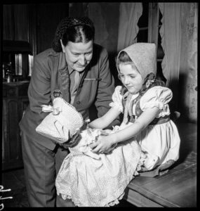 Bonney gives a young girl a doll during relief efforts in Ammerschwihr, France.
