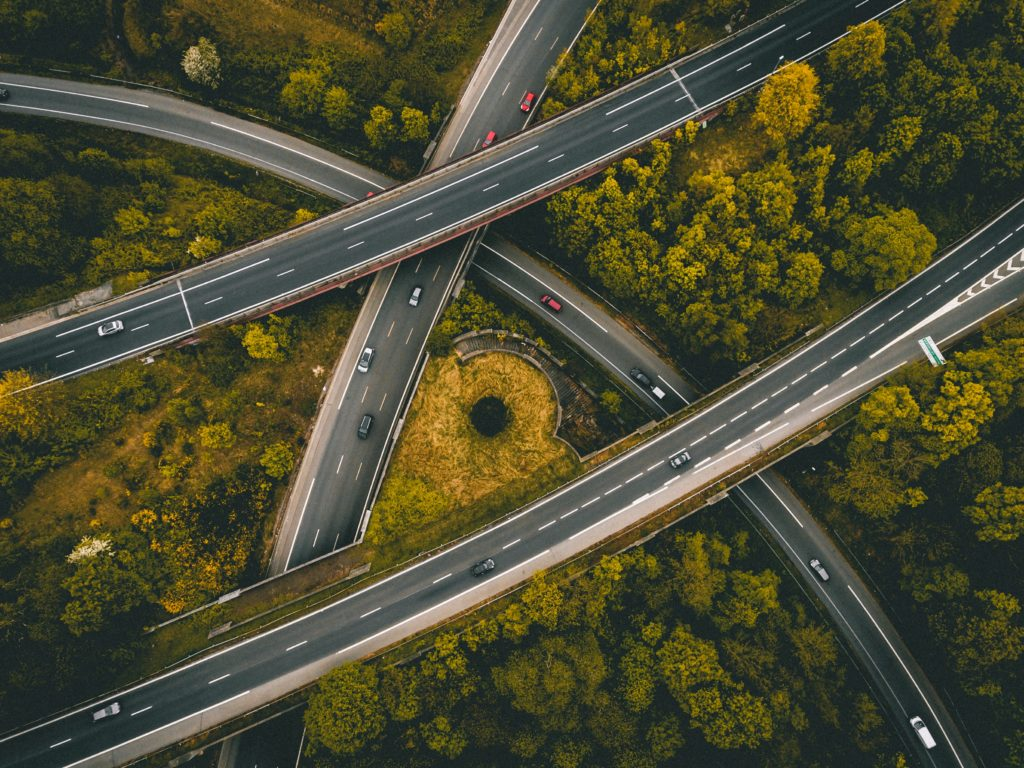 Birds-eye view of intersecting highways surrounded by trees