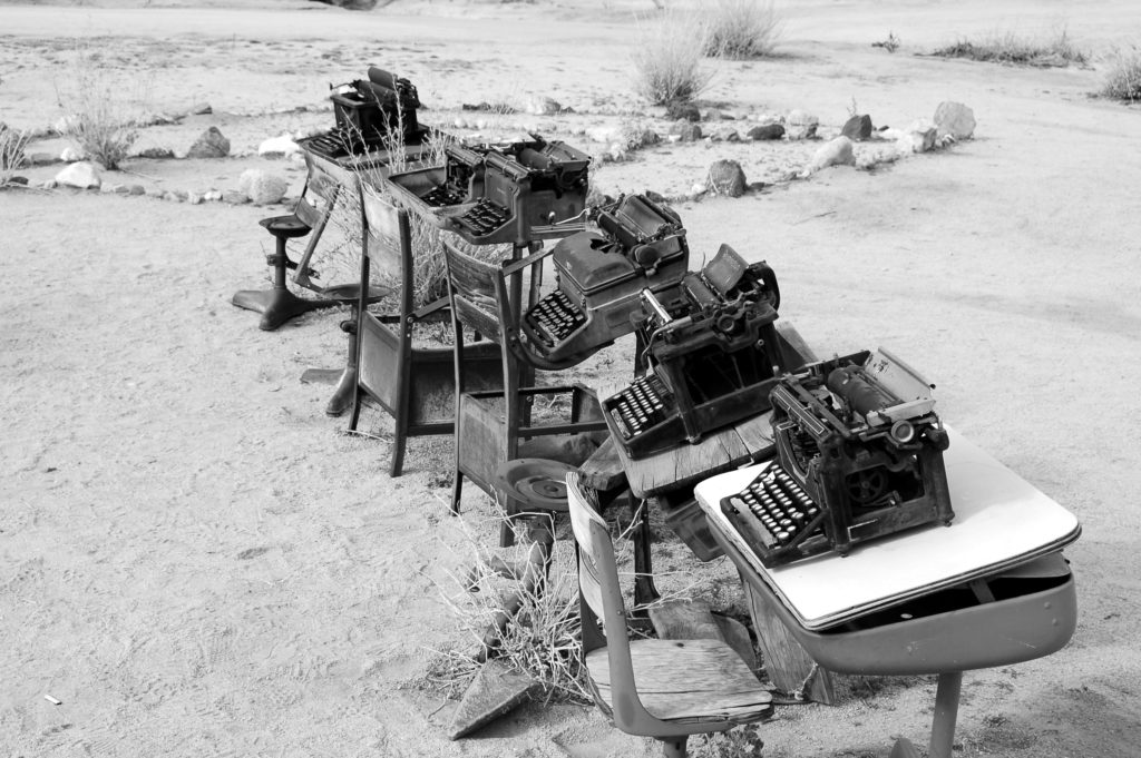 Typewriters resting on old school desks in a desert landscape