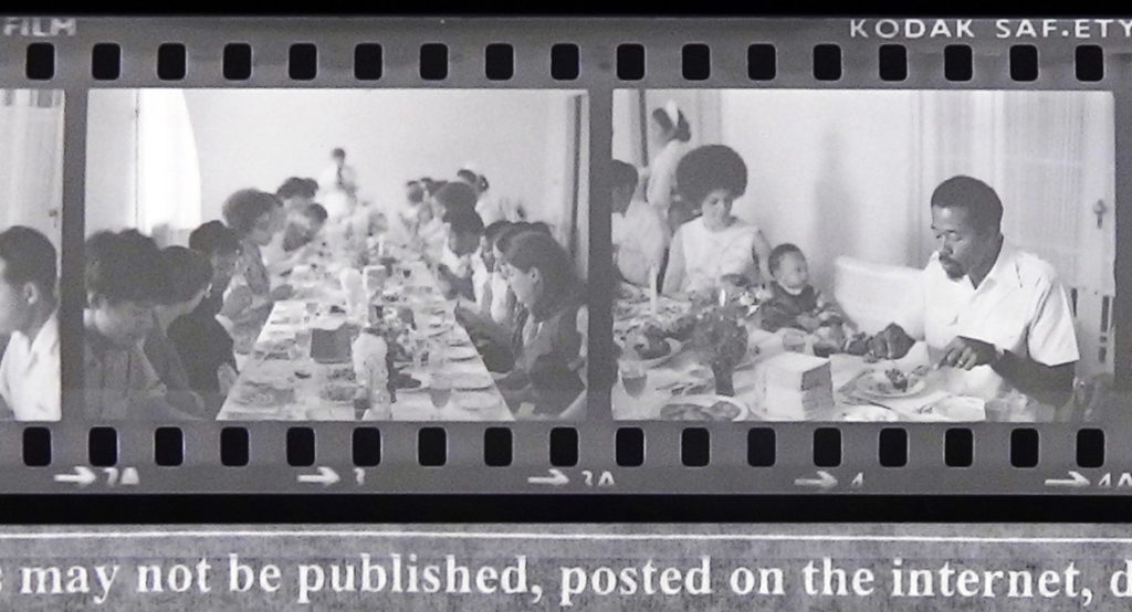 Two 35mm photo negatives, inverted to positive, showing Eldridge Cleaver and family at a dinner party in North Korea.