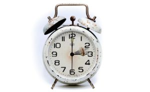 Old alarm clock, white, with rusty hands and bells.