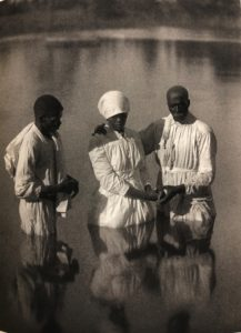 Photograhy by Doris Ullman of three African Americans standing in a river or pond for a baptism.