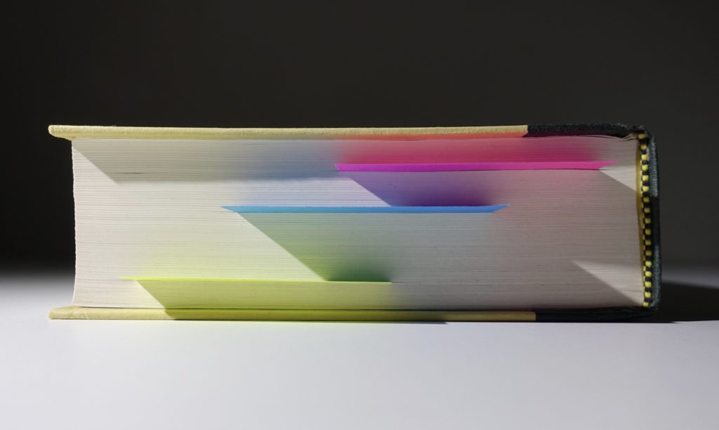 Photograph of a book on its side with sitckies protruding from the pages