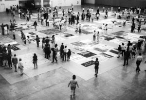 Photograph shows the AIDS memorial quilt laid out in groupings on the floor. Dozens of people wander around the perimeter of the groupings.