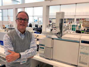Michael R. Schilling standing next to a gas chromatography/mass spectrometry instrument in the Materials Characterization laboratory at the Getty Conservation Institute in 2019.