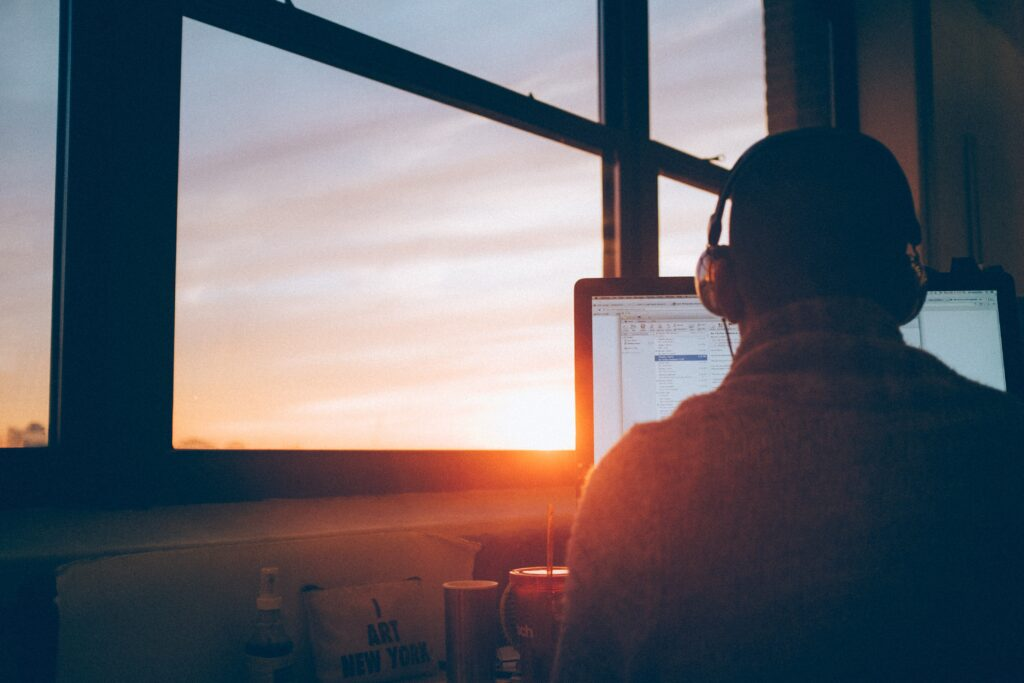 Person sitting in front of a computer screen with sunset in the background.