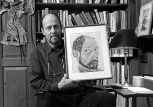 This is a black and white photo of James C. Scott holding a self portrait in his office