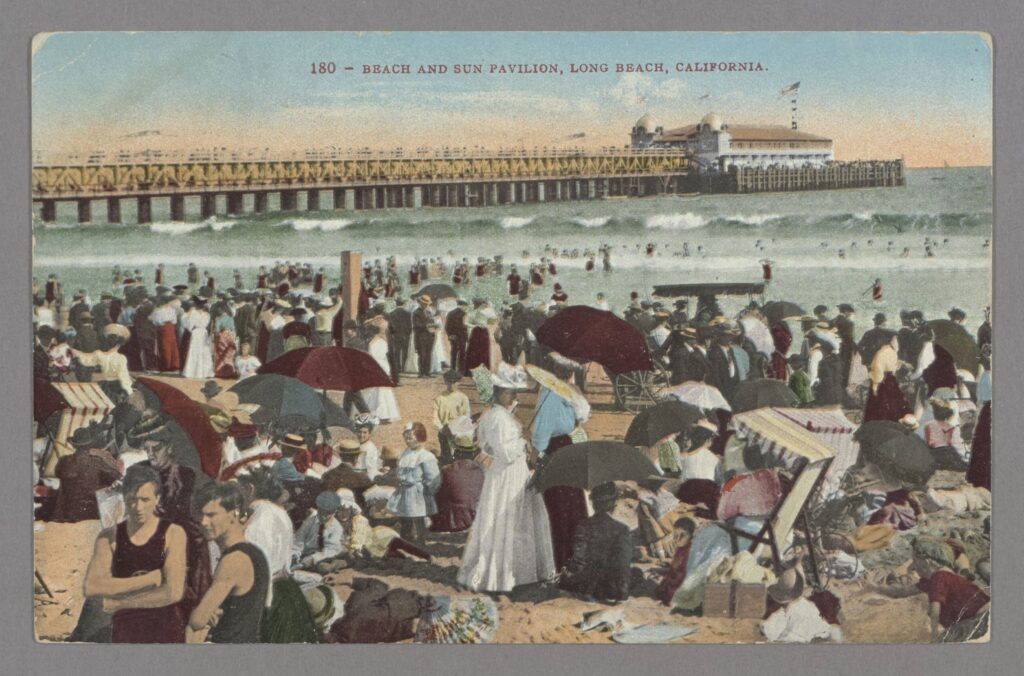 Color postcard of well-dressed crowds on the beach at Long Beach, with pier in background, circa 1905