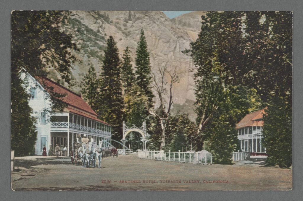 Color postcard, circa 1905, of the exterior of a Victorian hotel on the floor of Yosemite Valley, among evergreen trees