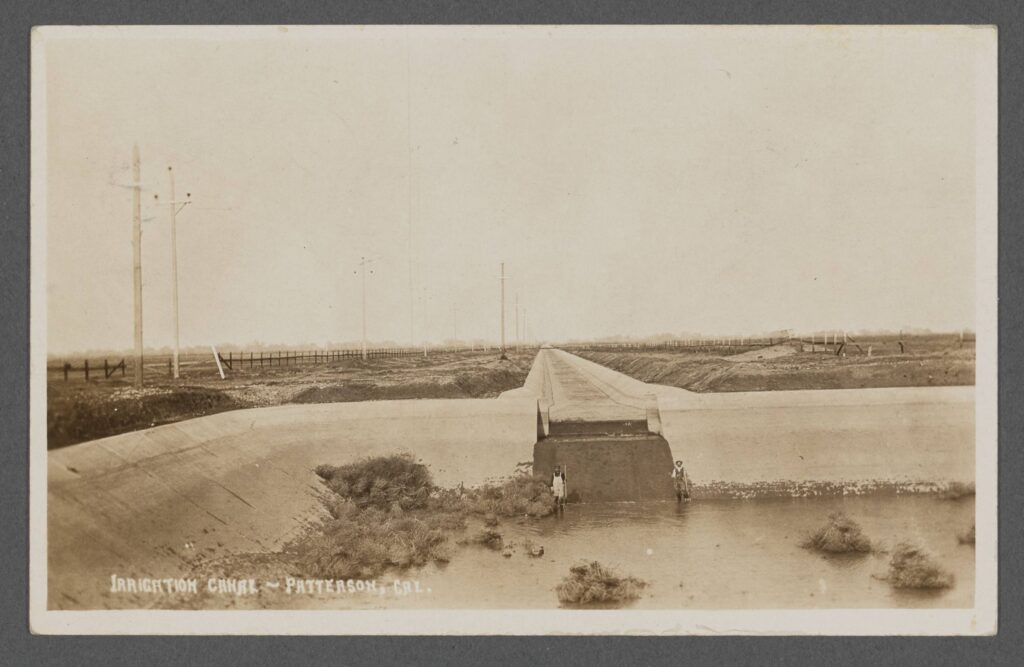 Black and white photographic postcard of a concrete irrigation canal in a flat and treeless landscape near Patterson, California