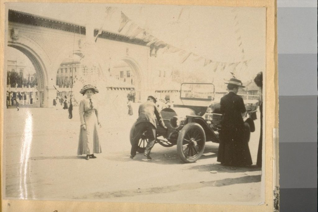 Black and white snapshot photograph of a woman posed near other people with an automobile, in front of entrance gates to the Alaska-Yukin-Pacific Exposition in 1909.