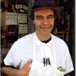 Eric Sartenaer wearing apron in front of store