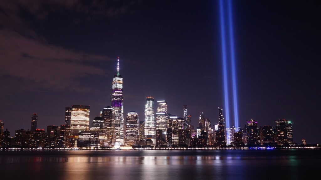 Night scene of New York City skyline with two beams of light where the twin towers once stood.